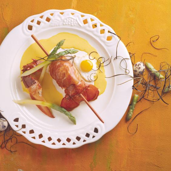 Spiesje van kreeft met groene asperges en Ganda Ham, gebakken kwarteleitje en safraansaus.
